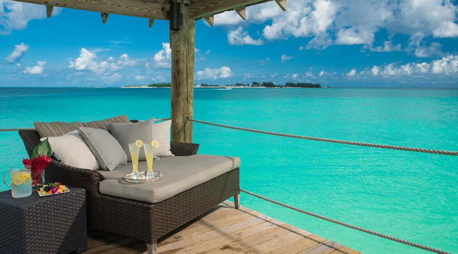 sandals island on a lounge chai over clear turquoise waters